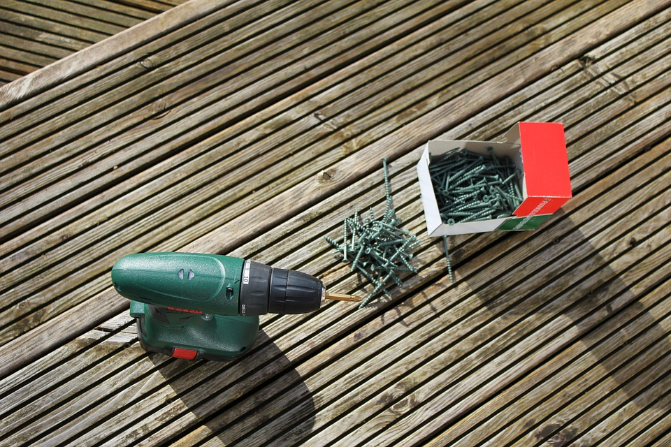 Electric drill and screws on a deck